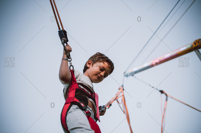 Young boy in trampoline harness