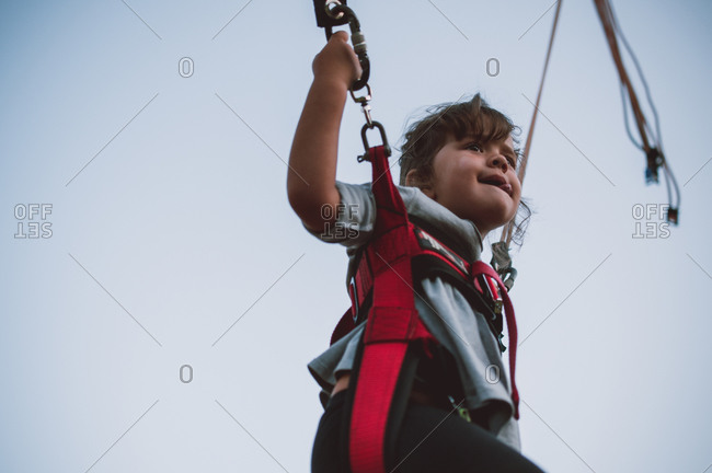 Low angle view of young girl jumping in trampoline harness