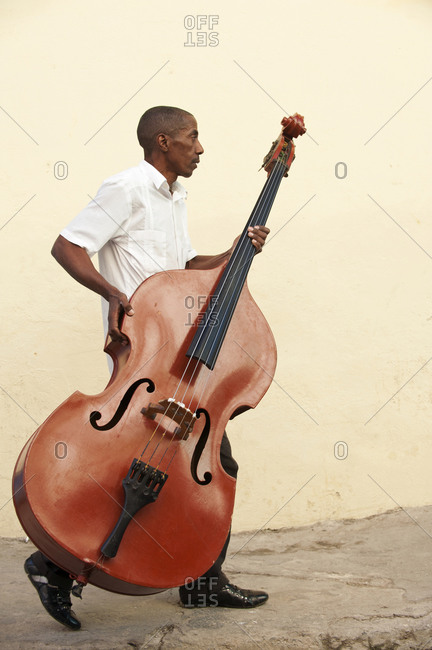 Havana, Cuba - January 26, 2010: Bass player carrying his instrument in Havana, Cuba