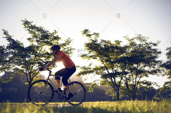 Man riding his bike through a park