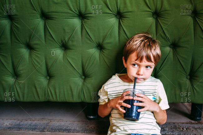 Little boy leaning against a green cushion sipping a drink