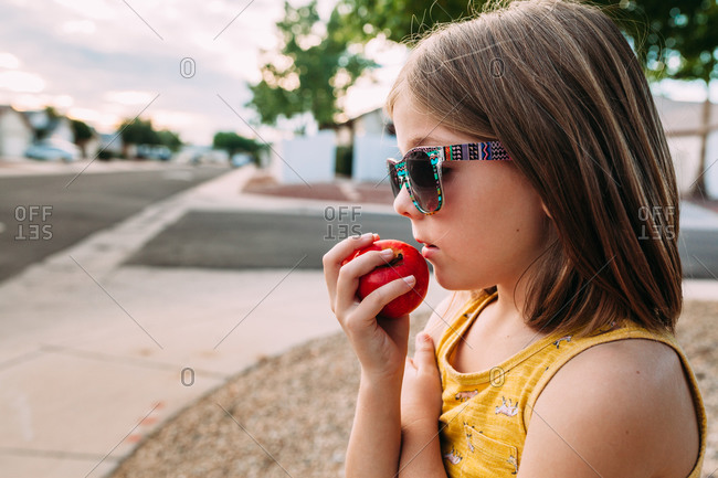 Little girl holding an apple to her mouth