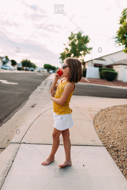Little girl standing on a sidewalk eating an apple