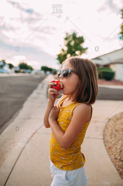 Little girl on a sidewalk eating an apple
