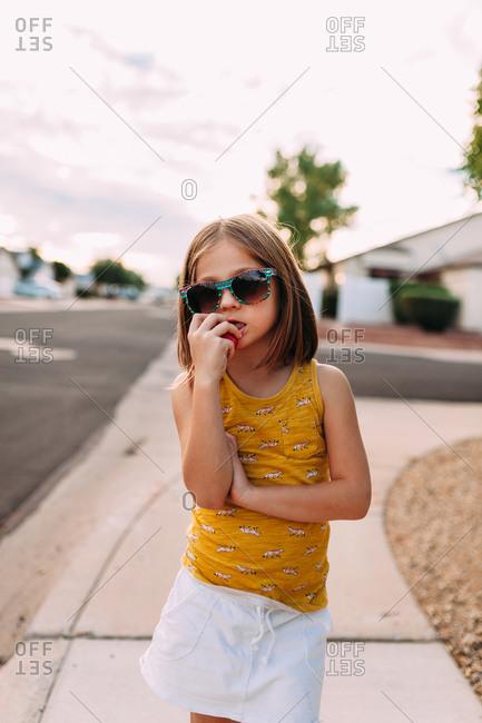Little girl standing on a sidewalk biting an apple