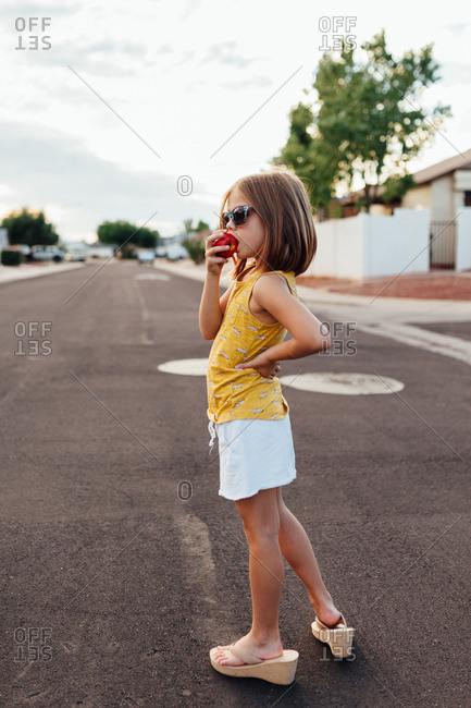 Little girl standing in a street eating an apple