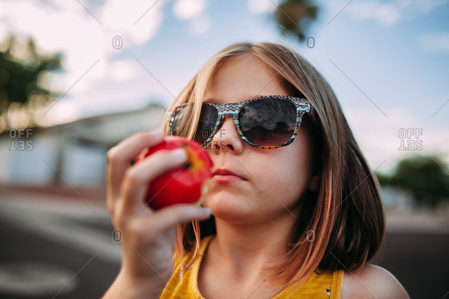 Little girl holding a bitten apple