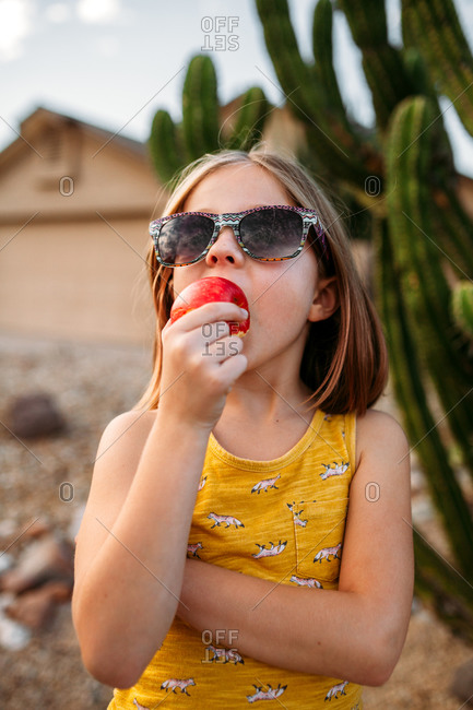 Little girl eating an apple in front of a cactus