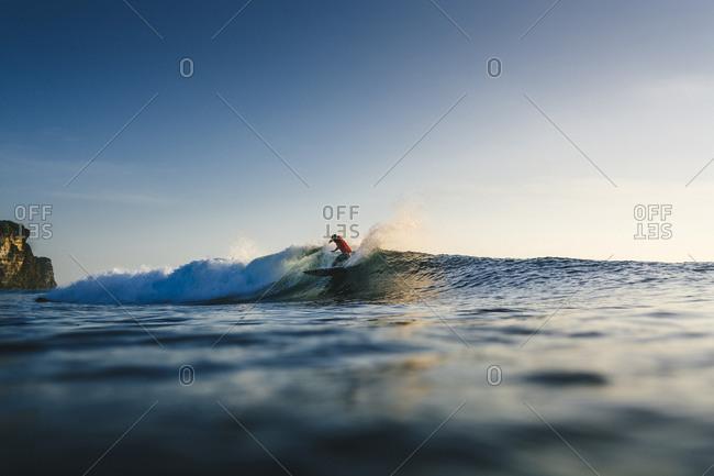Surfer riding wave in Uluwatu, Bali