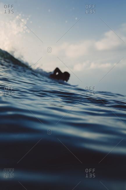 Surfer paddling wave in Uluwatu, Bali