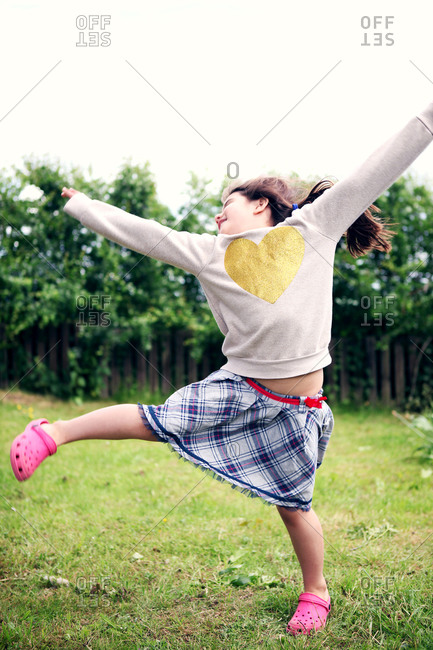 Girl dancing outside with arms up in the air