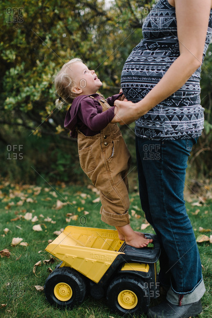 Young child standing on toy truck while holding pregnant mother's hands