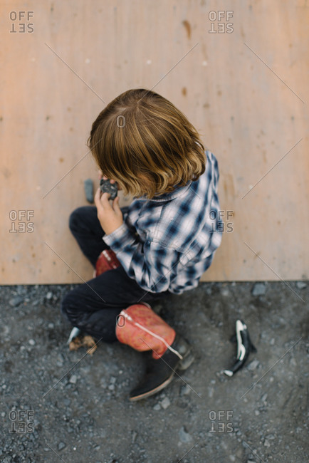 Overhead view of young boy playing on a wooden ramp