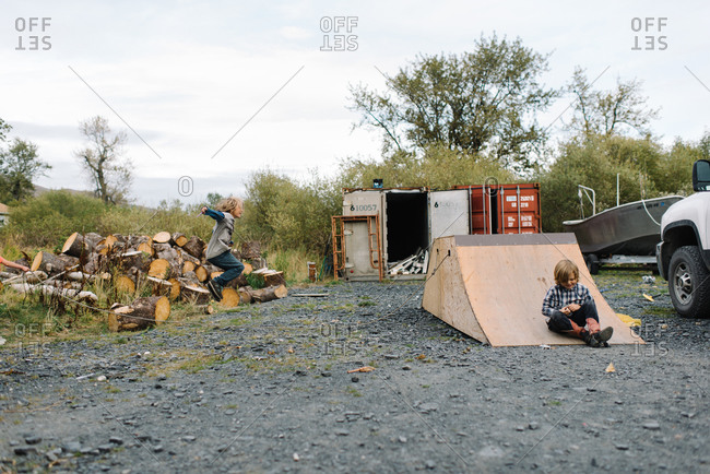 Two young boys playing in rural dirt and gravel lot