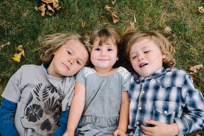 Overhead view of two young boys lying on grass with their younger sister