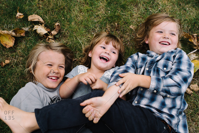 Three playful young siblings rolling around on grass