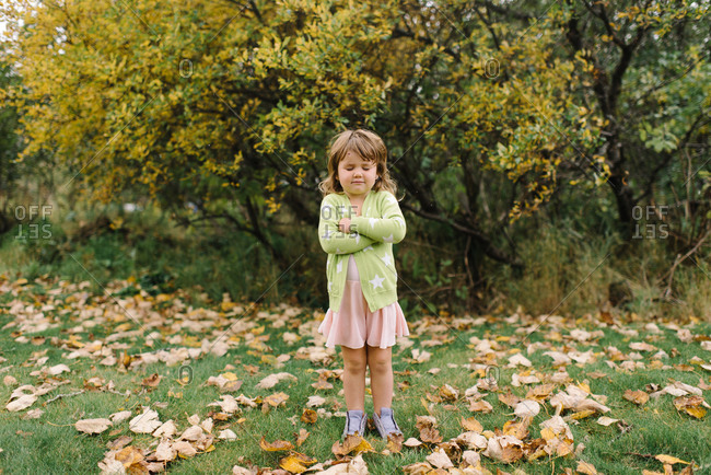 Cute young girl with arms crossed and eyes closed standing in backyard