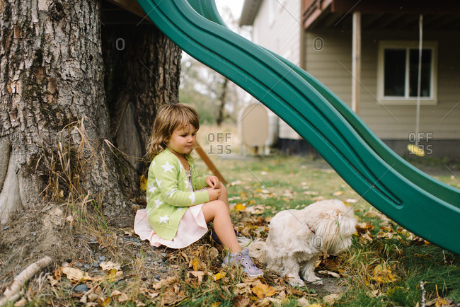 Young girl sitting under backyard slide with dog