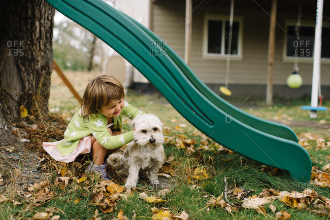 Young girl petting her dog under backyard slide
