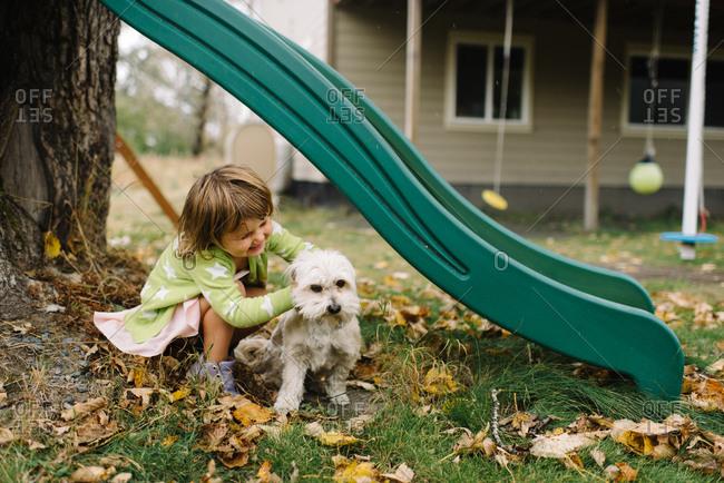 Young girl petting her dog under backyard slide
