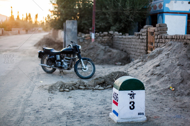 Shey, Ladakh, India - August 27, 2010: Motorcycle parked on side of dirt street