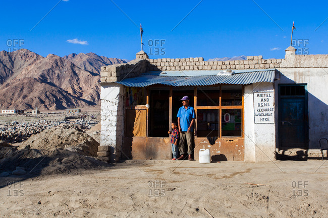 Shey, Ladakh, India - August 28, 2010: Man and child standing in front of a store