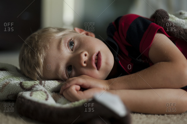 Little boy lying on a fleece coat on floor