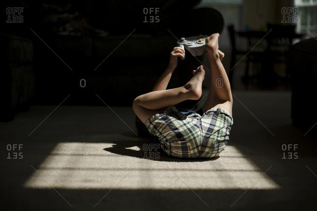 Boy on floor in sunlight holding game controller