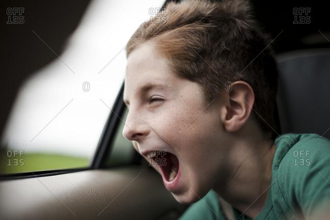 Boy yelling out open window in a car