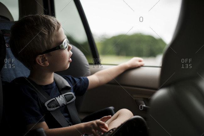 Little boy in sunglasses gazing out car window