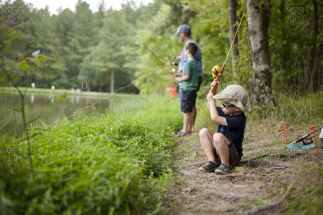 Two young boys and man fishing in rural water