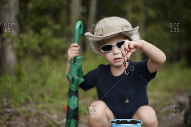 Boy holding worm for fishing bait