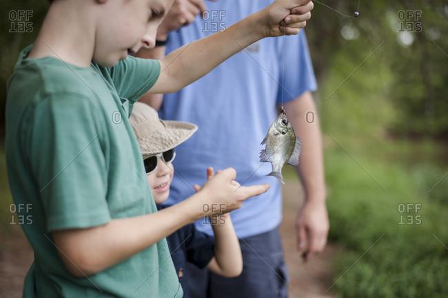 Kids and man looking at freshly caught fish