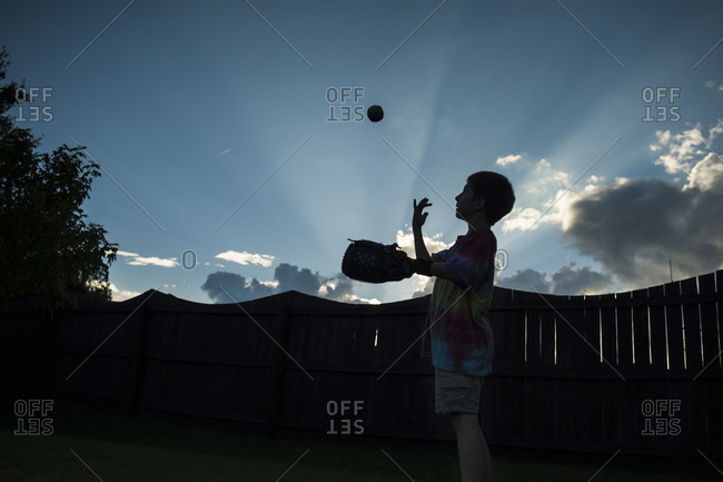 Silhouette of boy in yard tossing baseball in air