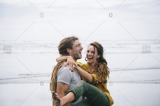 Happy couple with dreadlocks on the beach