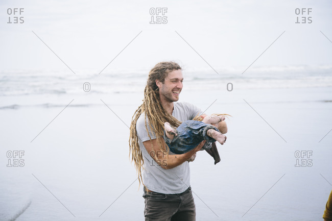 Father with dreadlocks spinning son on the beach
