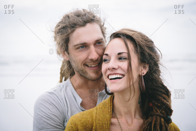 Happy couple with dreadlocks smiling on the beach