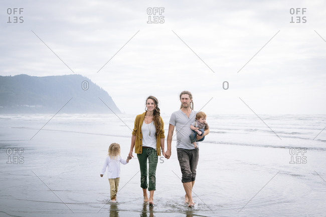 Family holding hands walking on the beach