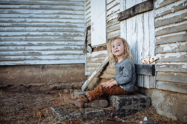 Young blonde boy sitting on steps