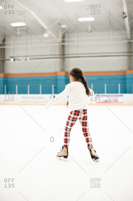 Little girl ice skating at a rink