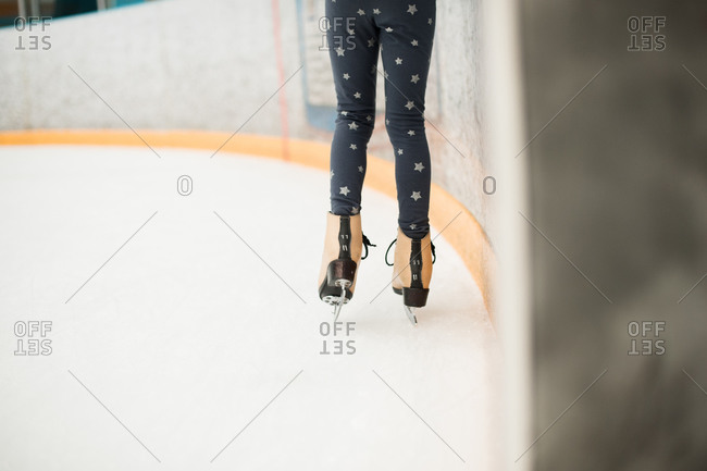 Legs of a little girl in an ice skating rink