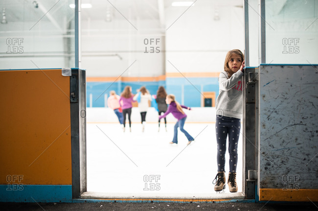 Little girl standing at the entrance to an ice rink