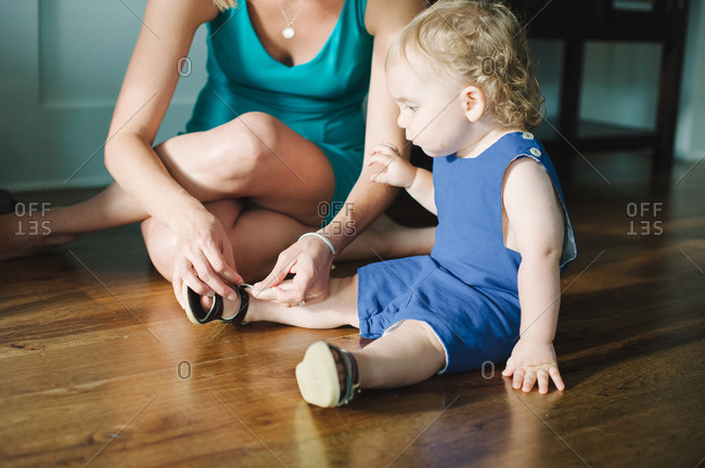 A mother puts sandals on her toddler