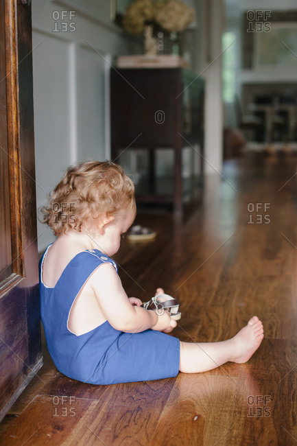 A little girl looks at her sandal