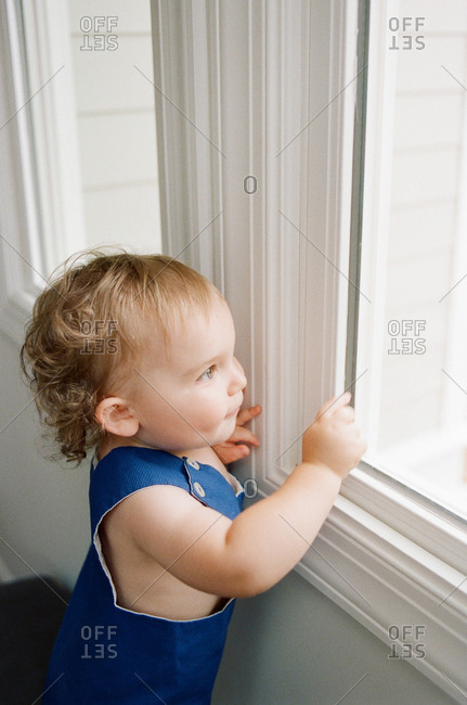 A little toddler looks out of a window