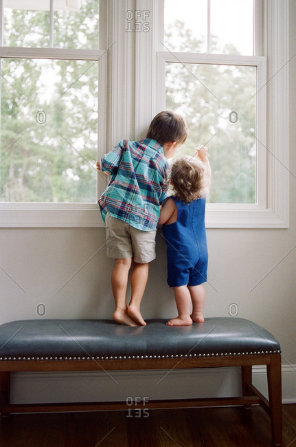 Siblings stand on a bench and look out the window