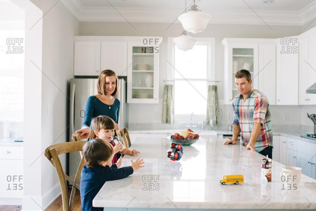 A family plays around their kitchen counter