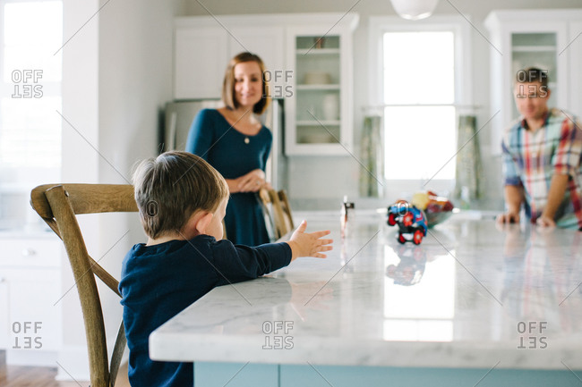 A boy spins a toy car at his kitchen counter