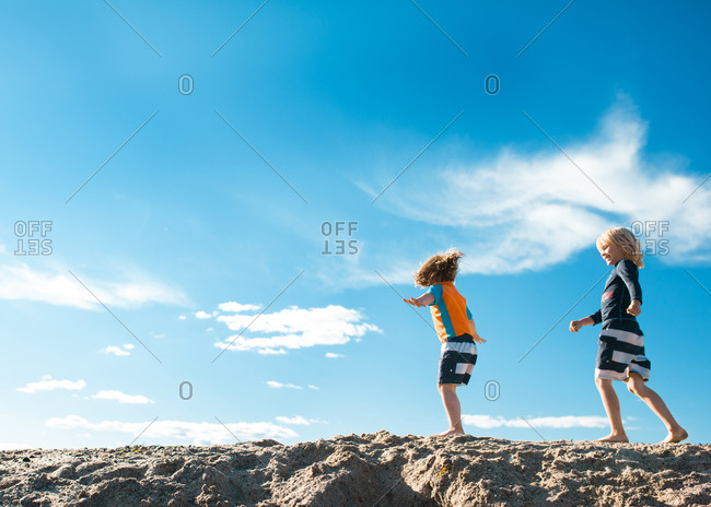 Two little boys running on the beach