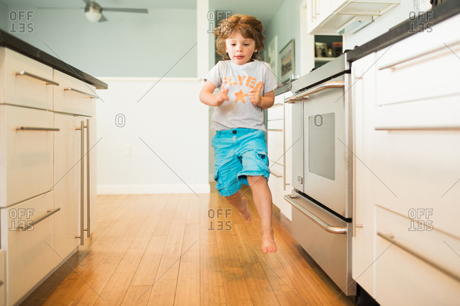 Young boy skipping/jumping through the kitchen